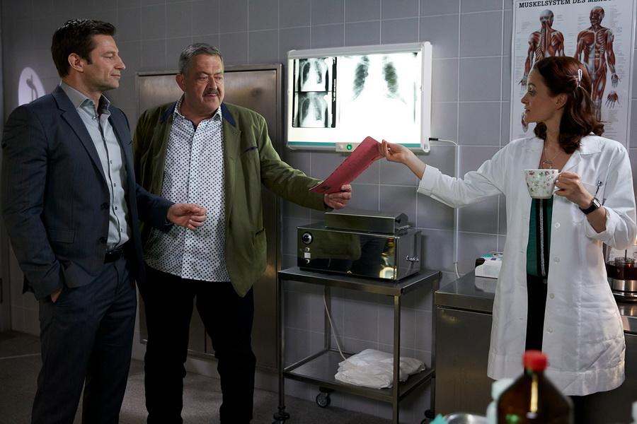 Die Kommissare Hofer (Joseph Hannesschläger, M.) und Hansen (Igor Jefti, l.) sind gespannt auf die Untersuchungsergebnisse von Pathologin Mai (Sina Wilke, r.).