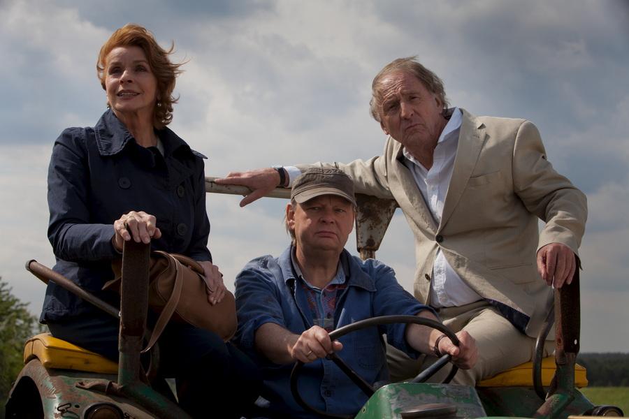 Leo (Günther Maria Halmer, r.) und Rita (Senta Berger) haben sich auf den engen ländlichen Straßen verfahren. Nachbar Bernd (Fritz Roth, M.) schleppt das Paar schließlich ab.